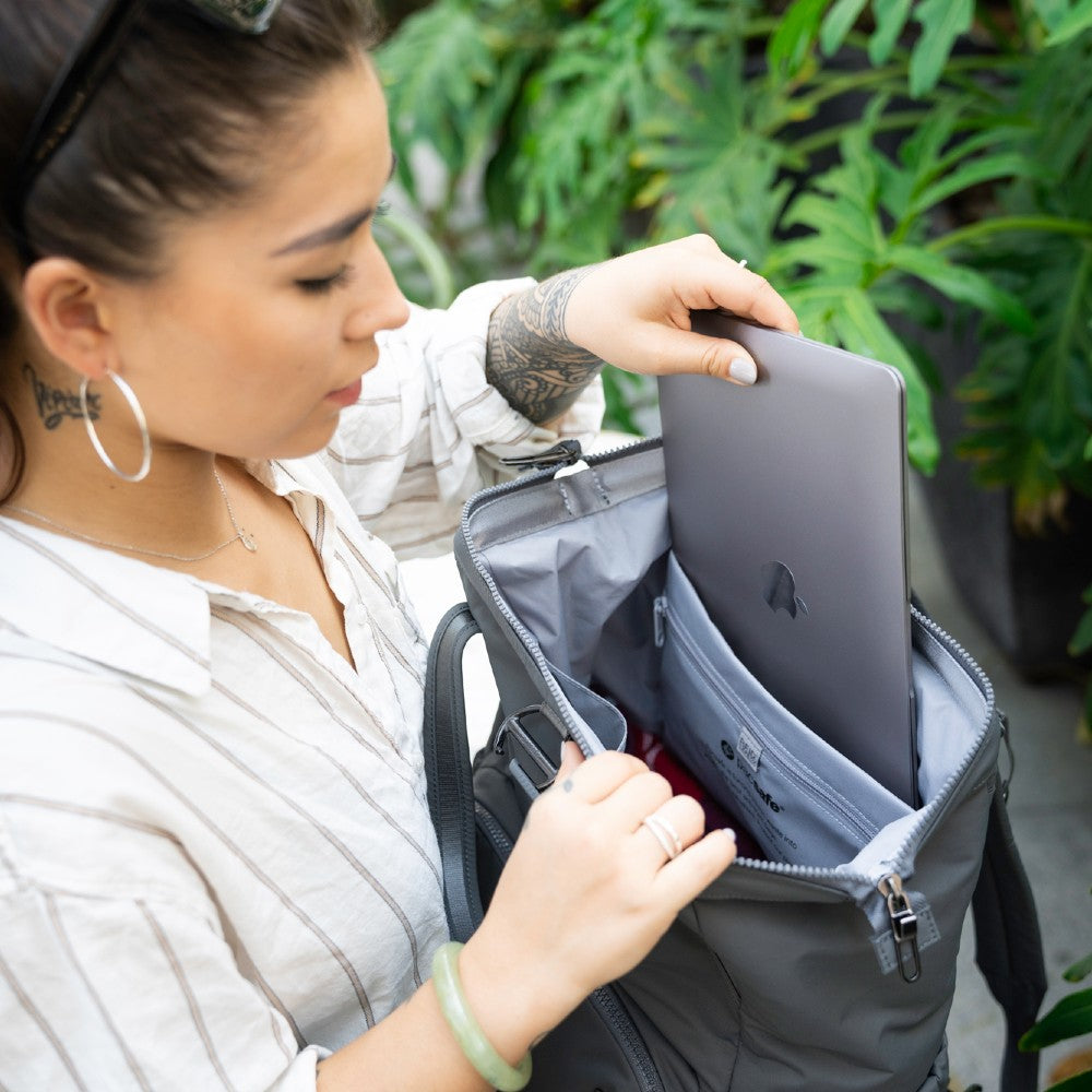 Woman inserting a laptop into the Pacsafe Citysafe CX Anti-Theft Backpack color Storm made with ECONYLu00ae regenerated nylon