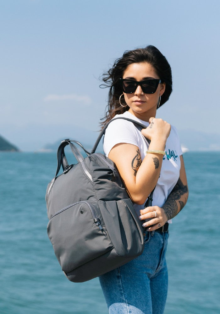 Woman travelling with the Pacsafe Citysafe CX Anti-Theft Backpack color Storm made with ECONYLu00ae regenerated nylon