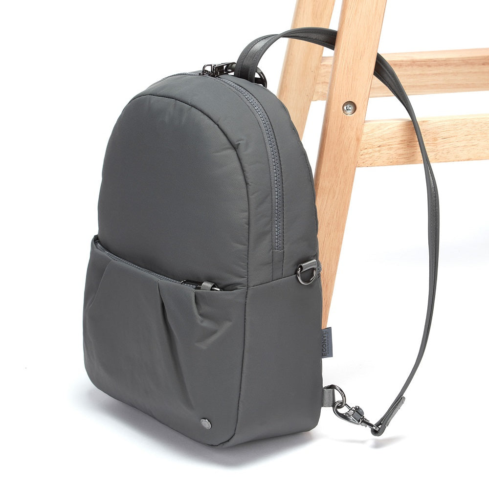 Side view of the Pacsafe Citysafe CX Anti-Theft Convertible Backpack color Storm made with ECONYLu00ae regenerated nylon locked to a chair