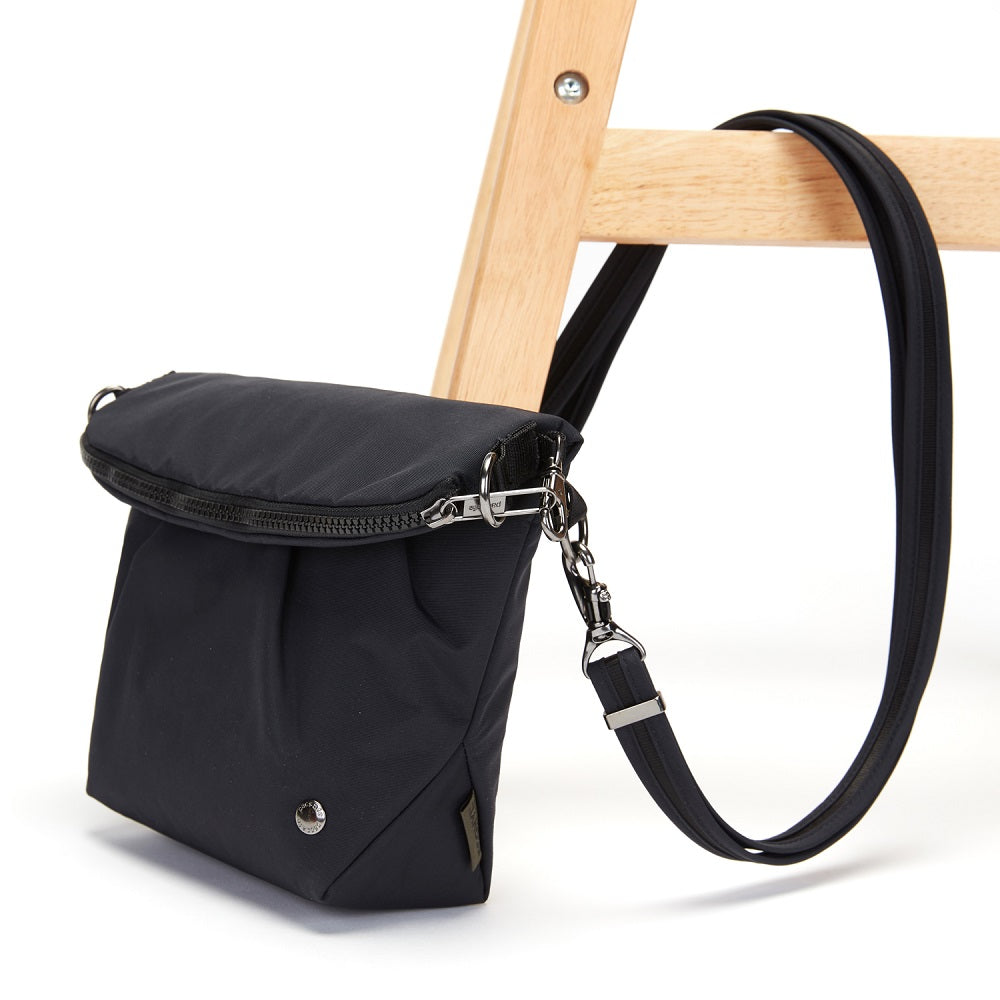 Side view of the Pacsafe Citysafe CX Anti-Theft Convertible Crossbody color Black made with ECONYLu00ae regenerated nylon locked to a chair