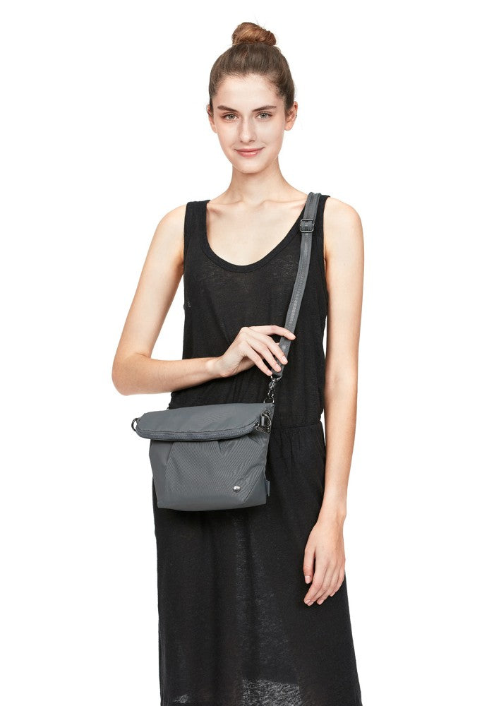Woman carrying the Pacsafe Citysafe CX Anti-Theft Convertible Crossbody color Storm made with ECONYLu00ae regenerated nylon