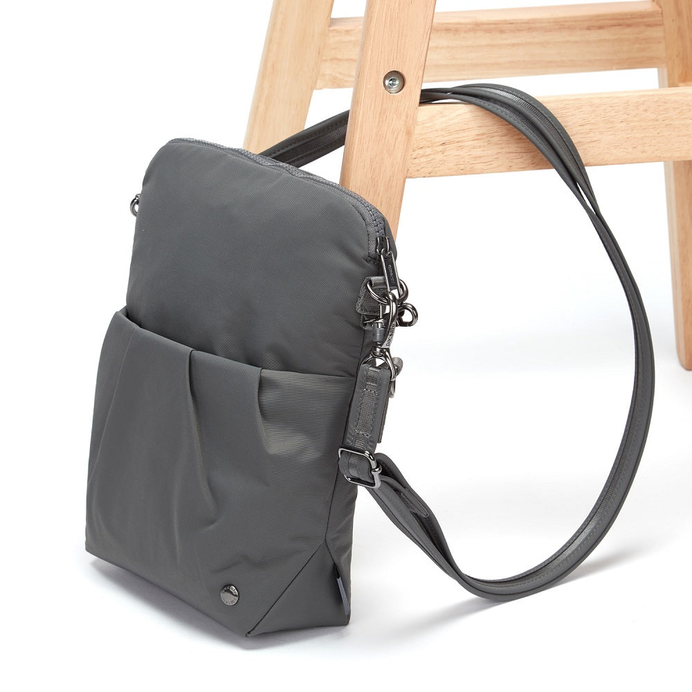 Side view of the Pacsafe Citysafe CX Anti-Theft Convertible Crossbody color Storm made with ECONYLu00ae regenerated nylon locked to a chair