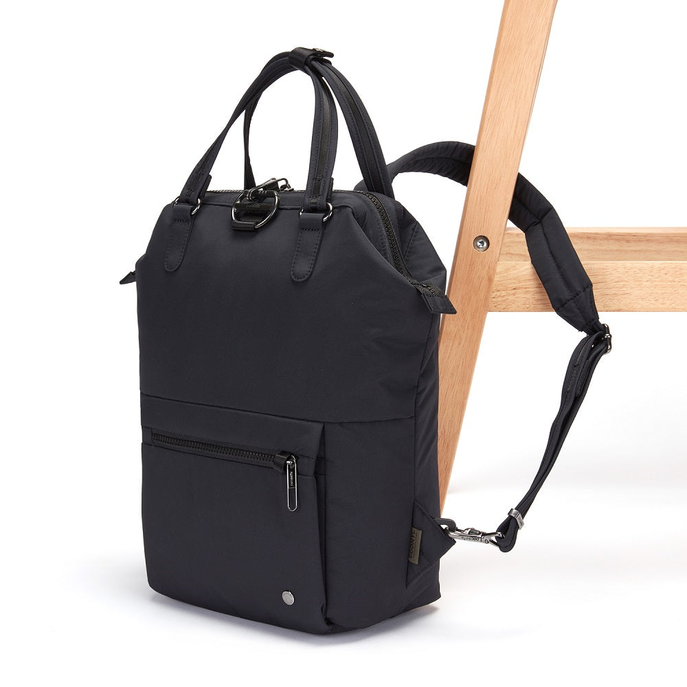 Side view of the Pacsafe Citysafe CX Anti-Theft Mini Backpack color Black made with ECONYLu00ae regenerated nylon locked to a chair