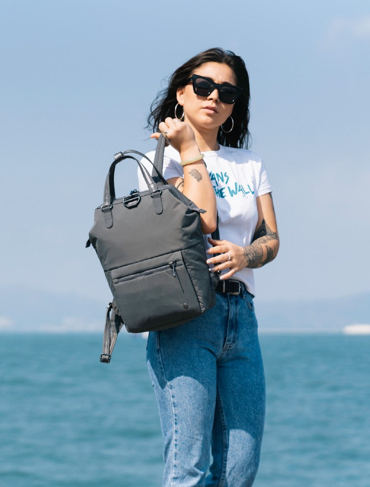 Woman travelling with the Pacsafe Citysafe CX Anti-Theft Mini Backpack color Storm made with ECONYLu00ae regenerated nylon lifestyle