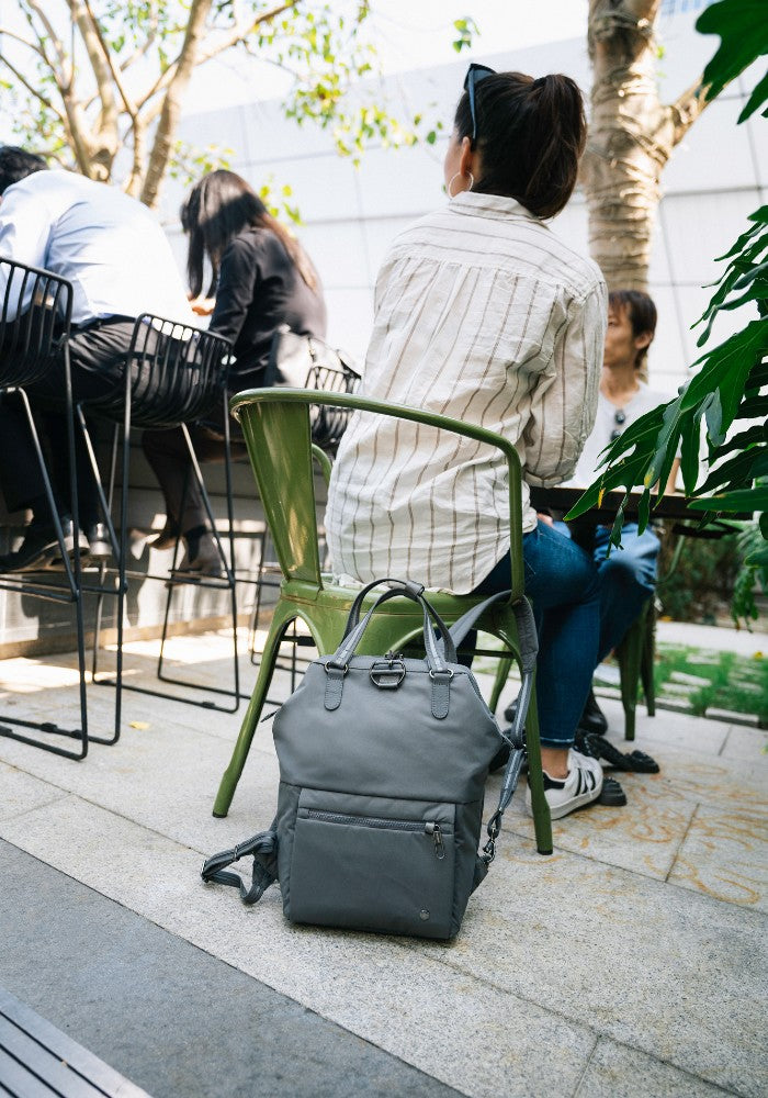 Woman sitting with the Pacsafe Citysafe CX Anti-Theft Mini Backpack color Storm made with ECONYLu00ae regenerated nylon locked to a chair