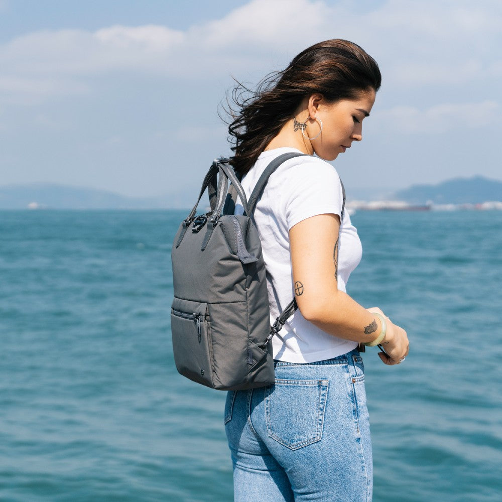 Woman travelling with the Pacsafe Citysafe CX Anti-Theft Mini Backpack color Storm made with ECONYLu00ae regenerated nylon