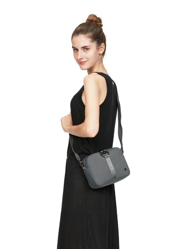 Woman carrying the Pacsafe Citysafe CX Anti-Theft Square Crossbody color Storm made with ECONYLu00ae regenerated nylon