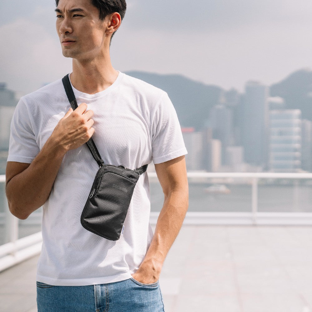 Man travelling with the Pacsafe Daysafe Anti-Theft Tech Crossbody color Black made with ECONYLu00ae regenerated nylon