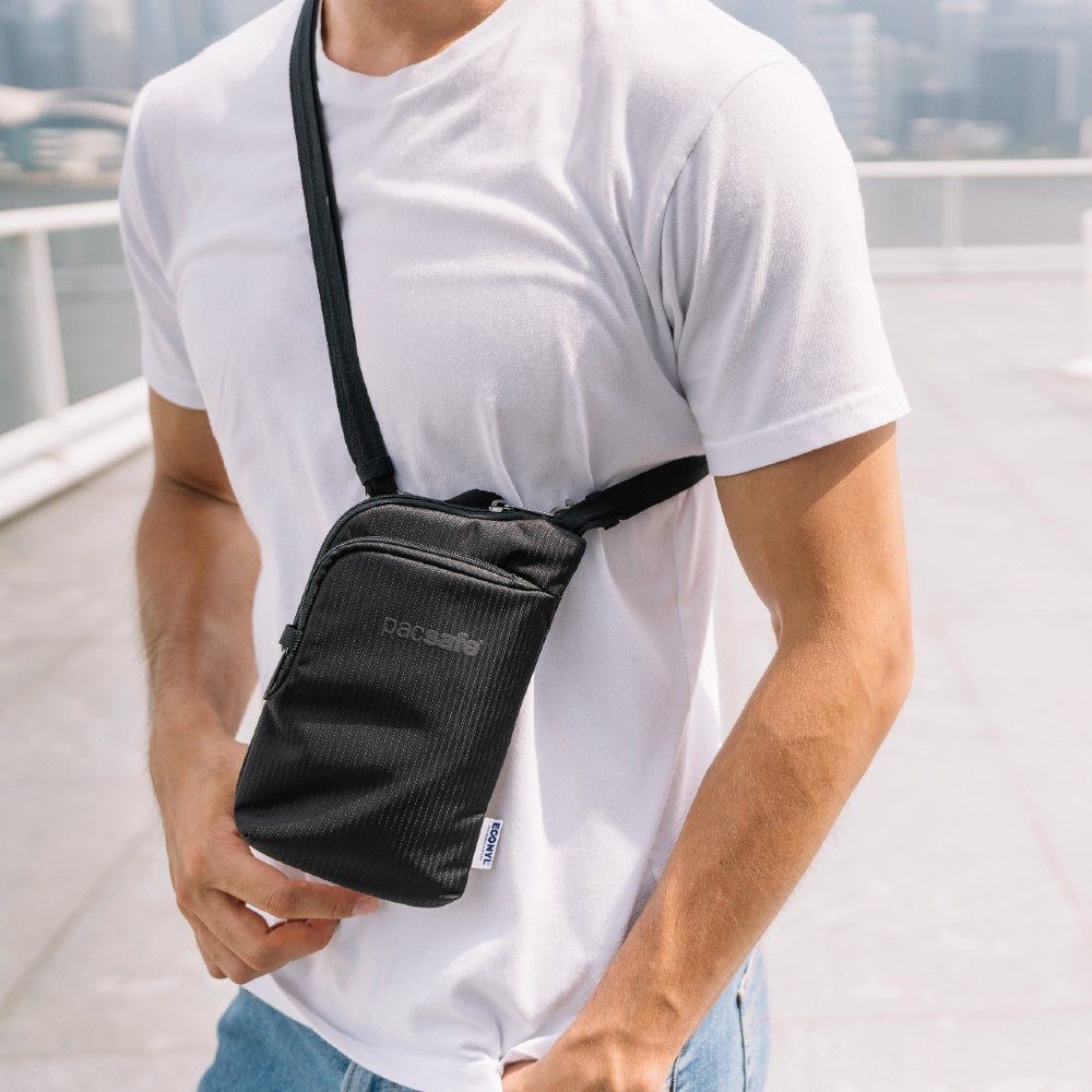 Man carrying the Pacsafe Daysafe Anti-Theft Tech Crossbody color Black made with ECONYLu00ae regenerated nylon