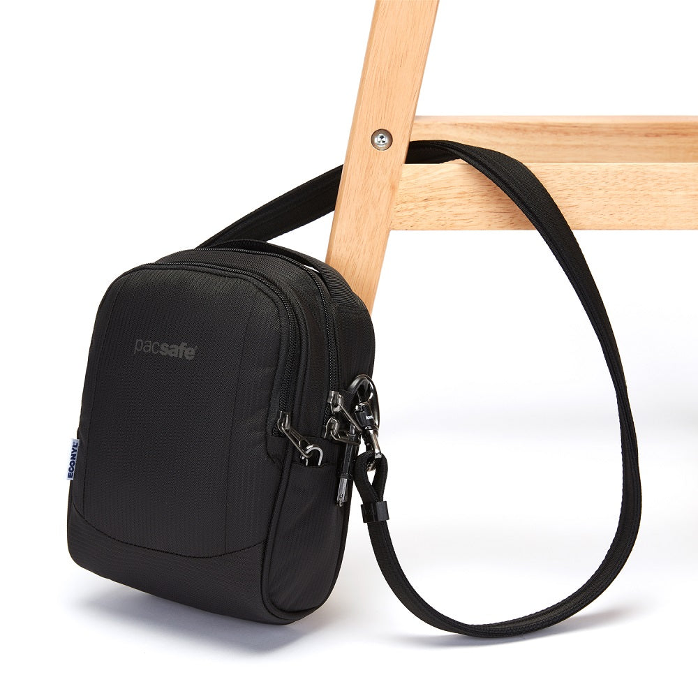 Side view of the Pacsafe Metrosafe LS100 Anti-Theft Crossbody Bag color Black made with ECONYLu00ae regenerated nylon locked to a chair