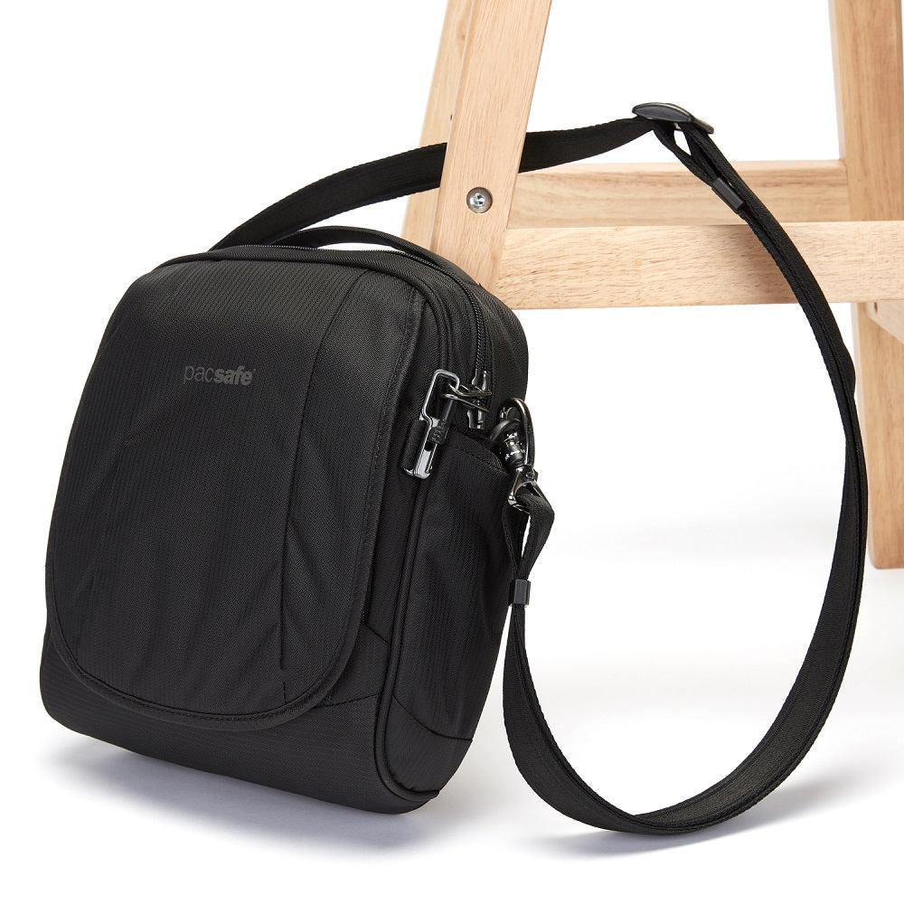 Side view of the Pacsafe Metrosafe LS200 Anti-Theft Crossbody Bag color Black made with ECONYLu00ae regenerated nylon locked to a chair