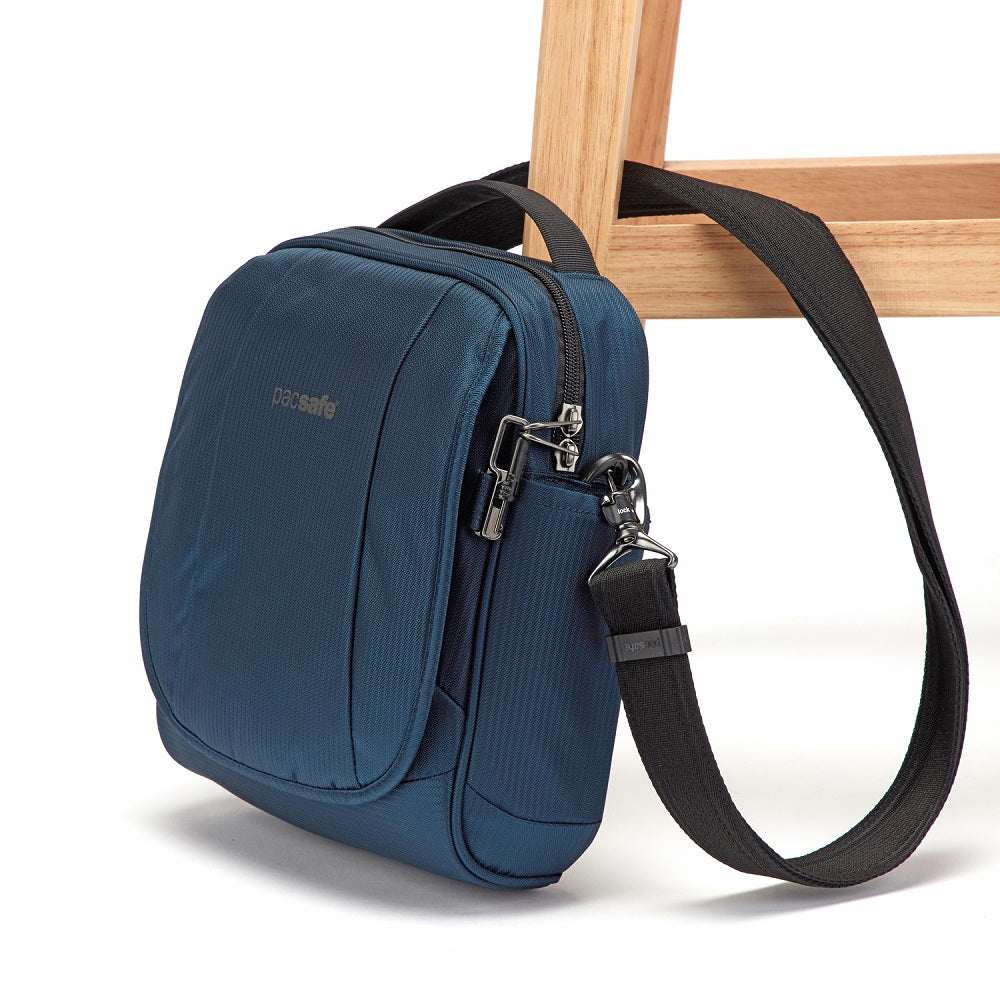 Side view of the Pacsafe Metrosafe LS200 Anti-Theft Crossbody Bag color Ocean made with ECONYLu00ae regenerated nylon locked to a chair