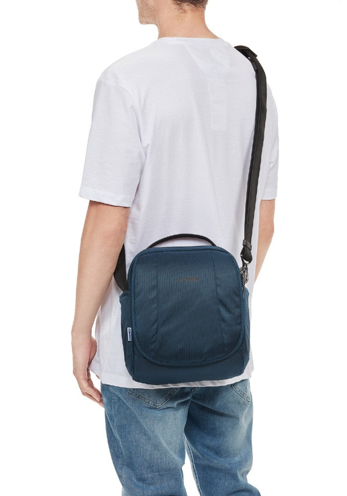 Man carrying the Pacsafe Metrosafe LS200 Anti-Theft Crossbody Bag color Ocean made with ECONYLu00ae regenerated nylon