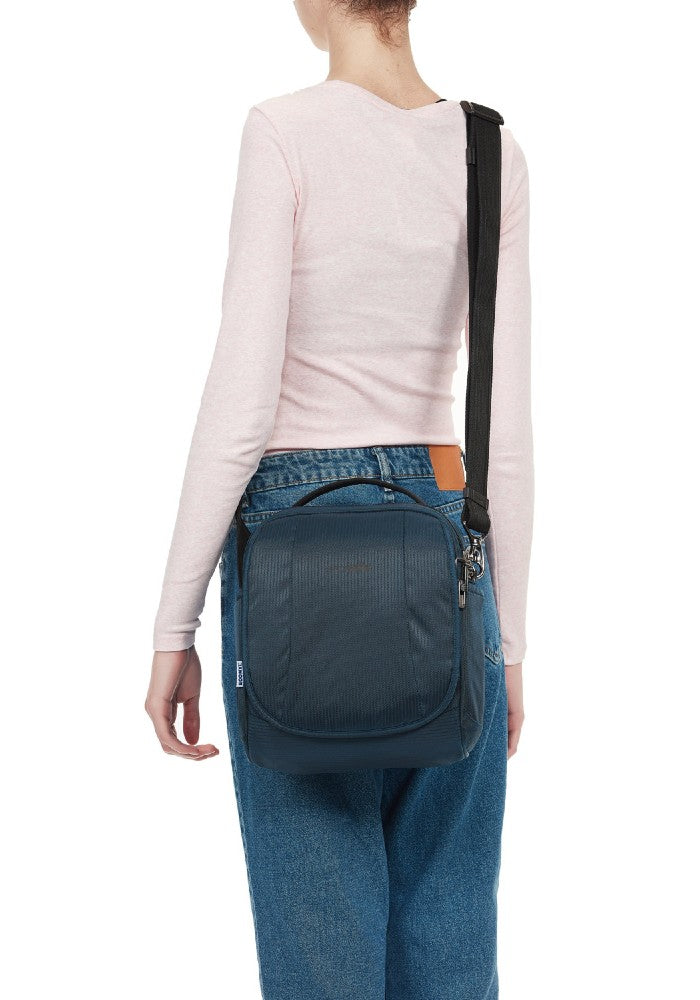 Woman carrying the Pacsafe Metrosafe LS200 Anti-Theft Crossbody Bag color Ocean made with ECONYLu00ae regenerated nylon