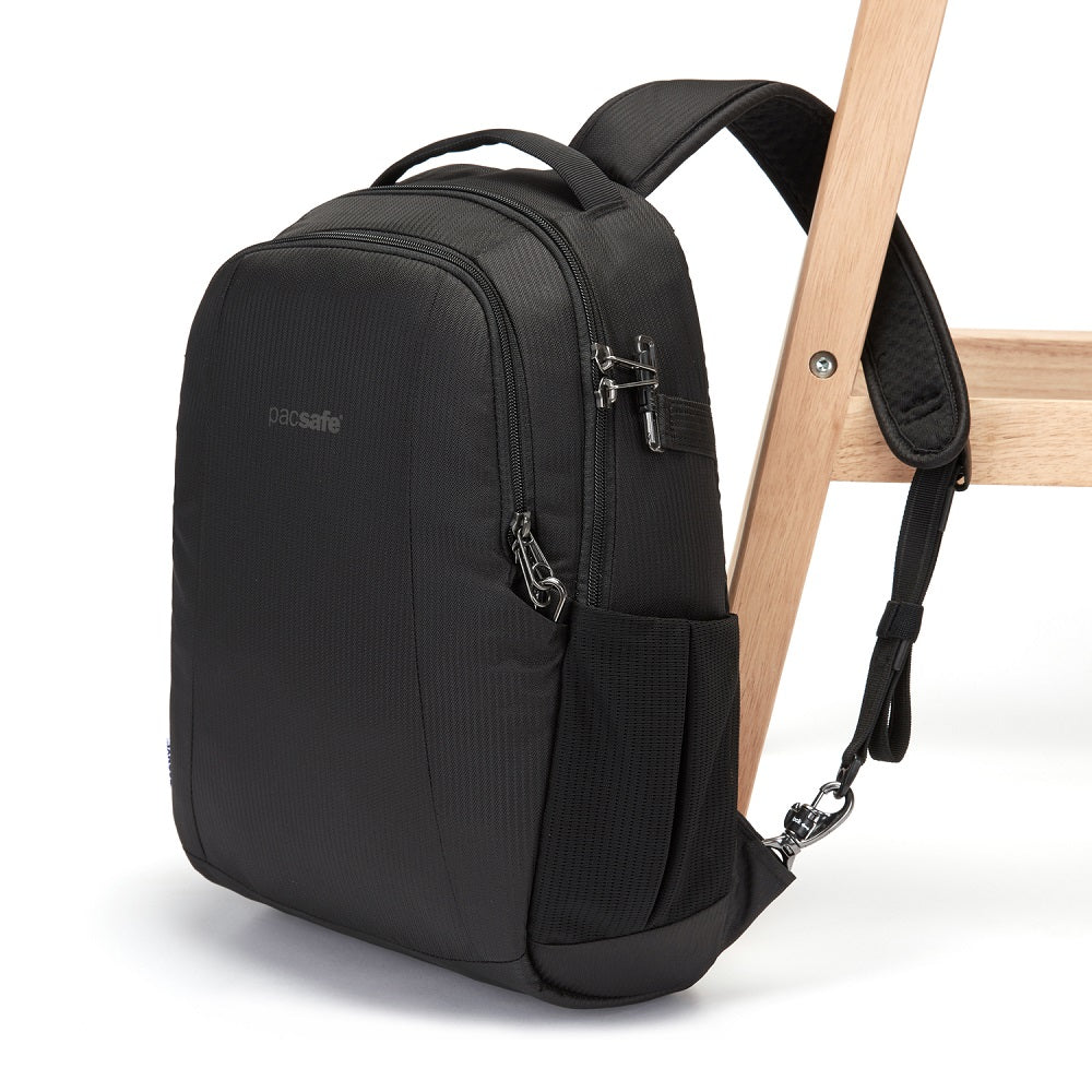 Side view of the Pacsafe Metrosafe LS350 Anti-Theft Backpack color Black made with ECONYLu00ae regenerated nylon locked to a chair