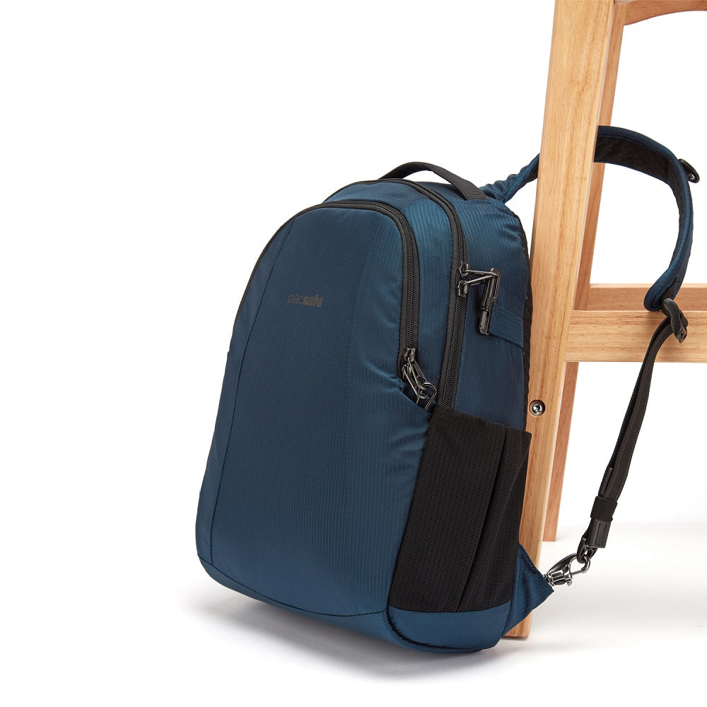 Side view of the Pacsafe Metrosafe LS350 Anti-Theft Backpack color Ocean made with ECONYLu00ae regenerated nylon locked to a chair
