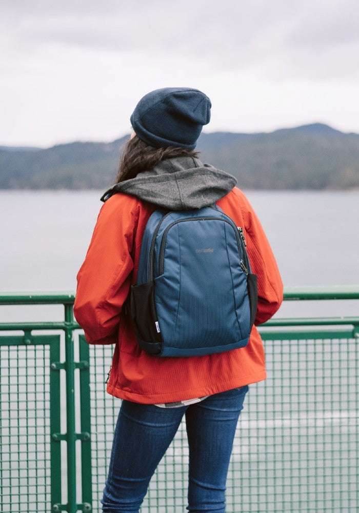 Woman travelling with the Pacsafe Metrosafe LS350 Anti-Theft Backpack color Ocean made with ECONYLu00ae regenerated nylon