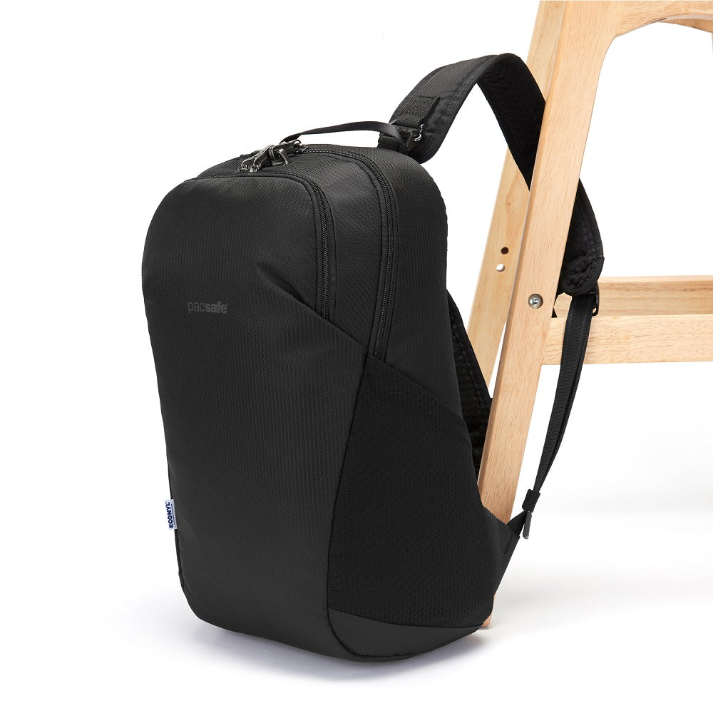 Side view of the Pacsafe Vibe 20L Anti-Theft Backpack color Black made with ECONYLu00ae regenerated nylon locked to a chair