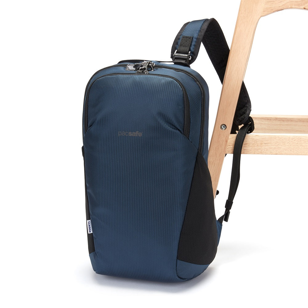 Side view of the Pacsafe Vibe 20L Anti-Theft Backpack color Ocean made with ECONYLu00ae regenerated nylon locked to a chair