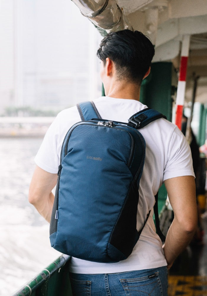 Man travelling with the Pacsafe Vibe 20L Anti-Theft Backpack color Ocean made with ECONYLu00ae regenerated nylon
