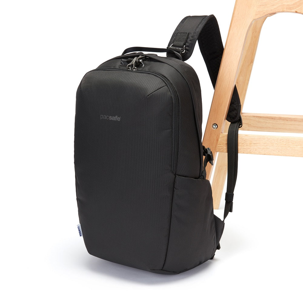 Side view of the Pacsafe Vibe 25L Anti-Theft Backpack color Black made with ECONYLu00ae regenerated nylon locked to a chair