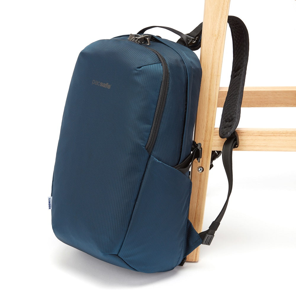 Side view of the Pacsafe Vibe 25L Anti-Theft Backpack color Ocean made with ECONYLu00ae regenerated nylon locked to a chair
