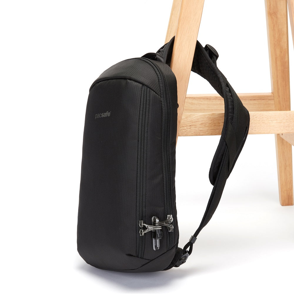 Side view of the Pacsafe Vibe 325 Anti-Theft Sling Pack color Black made with ECONYLu00ae regenerated nylon locked to a chair