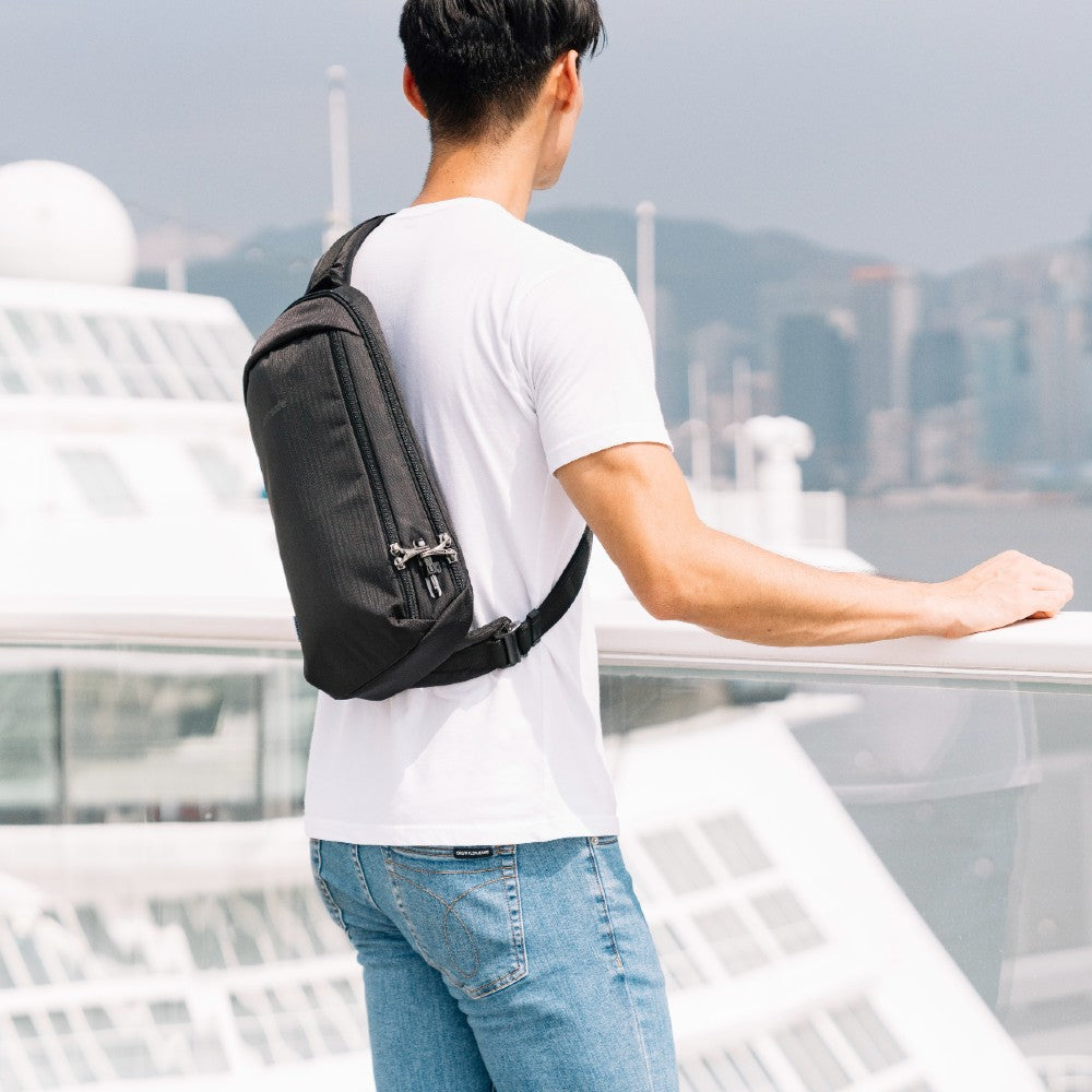 Man carrying the Pacsafe Vibe 325 Anti-Theft Sling Pack color Black made with ECONYLu00ae regenerated nylon