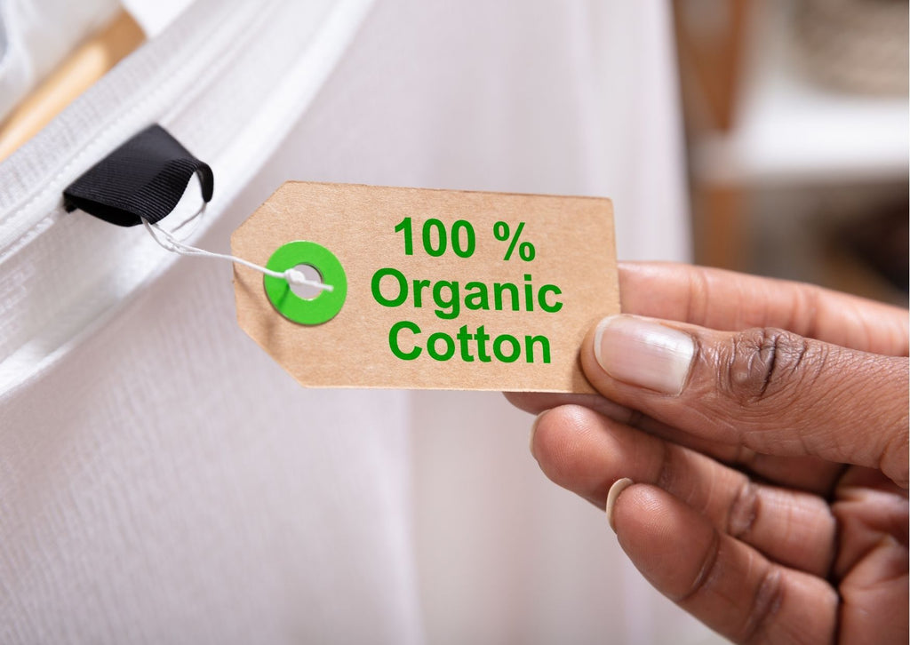 Close-up of a hand holding a tag attached to a white top on a hanger. The tag reads 100% Organic Cotton.