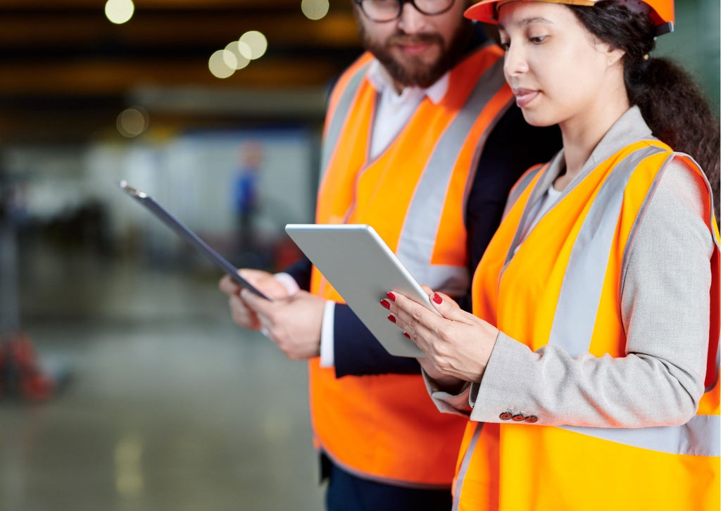 A man and a woman stood in a factory in hi-vis jackets and hard hats looking at clipboards