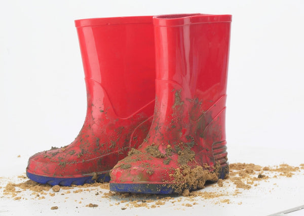 red kid's wellies covered in mud
