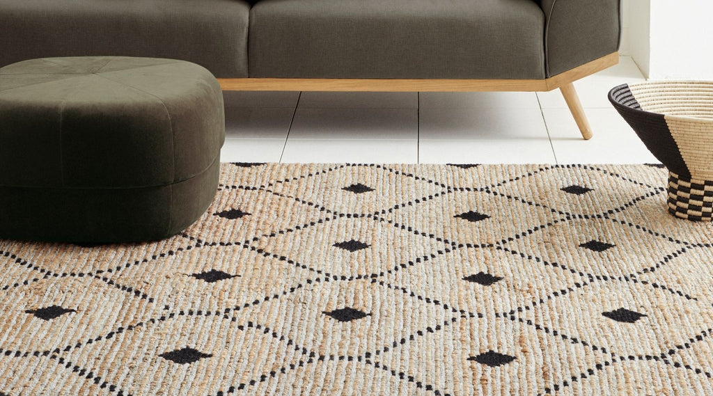 Weave patterned rug close up and styled with ottomon
