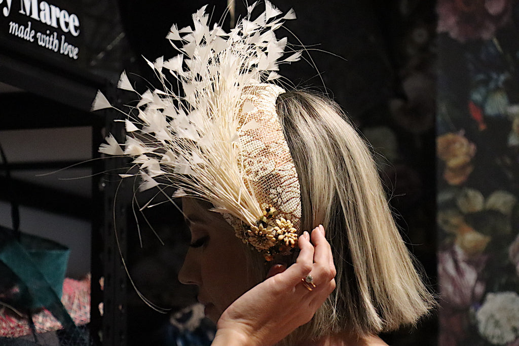Woman tries on a bridal headpiece at Dezignz By Maree millinery