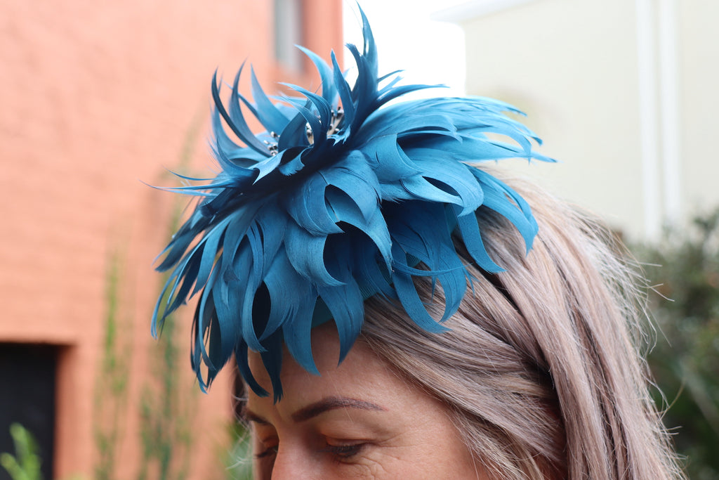 Woman in a blue feathered headpiece made by Dezignz By Maree millinery