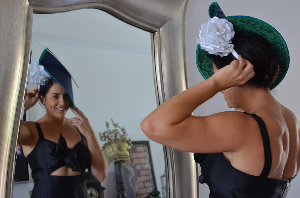 Woman in Dezignz By Maree hat looks at herself in a mirror