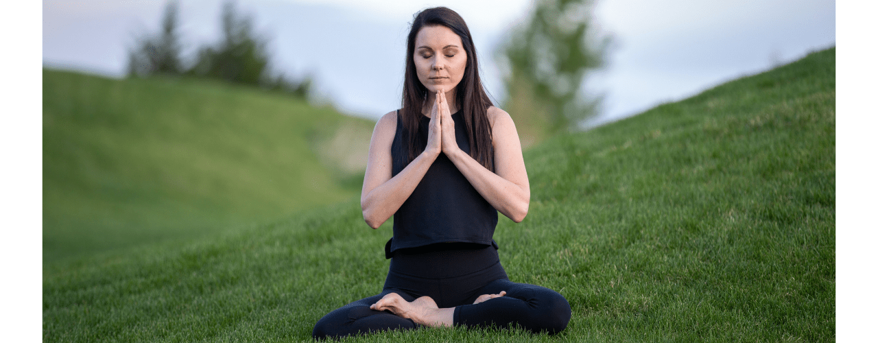 A lady sat on the ground in a yoga pose