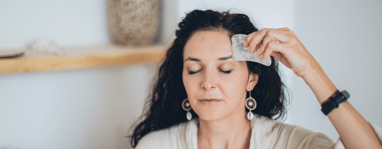 A lady using a gua sha tool on her face to give herself a gua sha facial massage