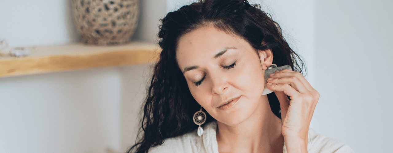 A lady giving herself a gua sha facial