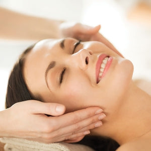 Woman receiving head and face massage as part of a special treatments package at a beauty salon