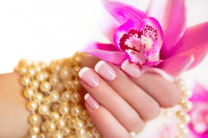 Woman's hand with French manicure gel powder aka clear acrylic nails