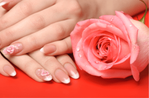 Woman's hands with flower designs on pink and white powder French manicure nails