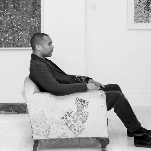 Portrait photograph of artist Robi Walters in his art studio gallery with mixed media art on display