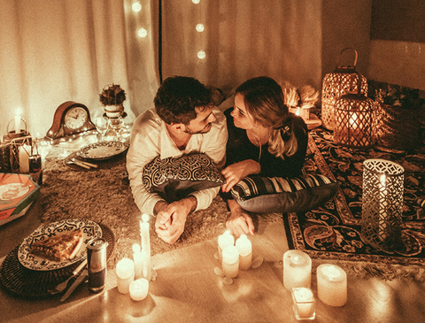 Couple staring into each others' eyes over candlelight