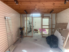 Shop interior with dividing wall stripped back to studs