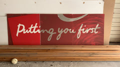 Dirty red sign that read 'putting you first'
