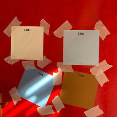 4 Paint samples stuck on a red wall. Periwinkle blue, light blue, cream white and dark brown