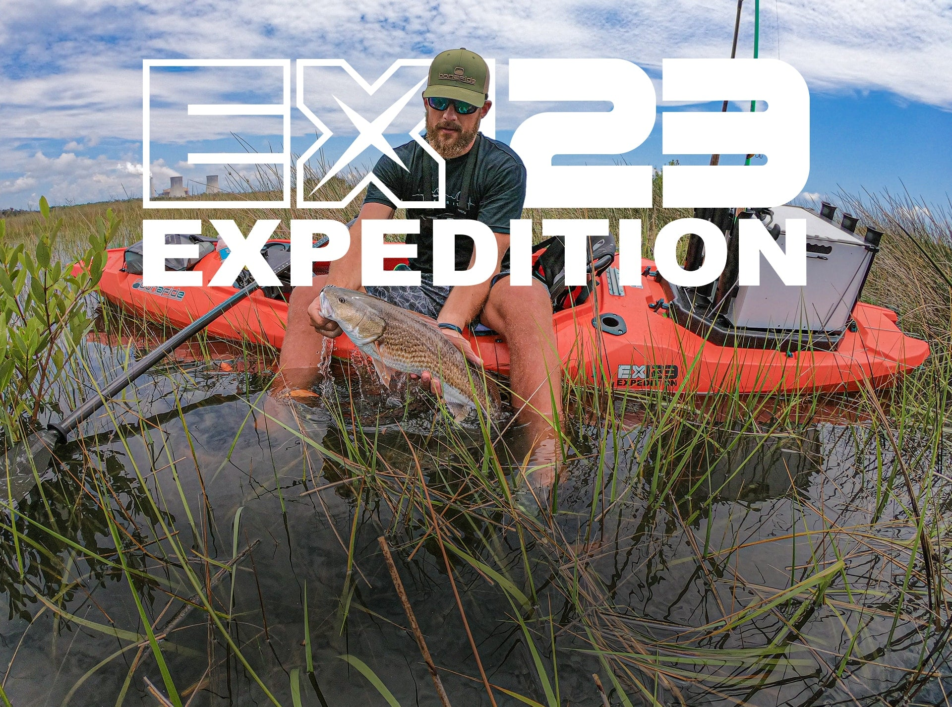 Angler sitting on edge of EX123 holding fish in the water