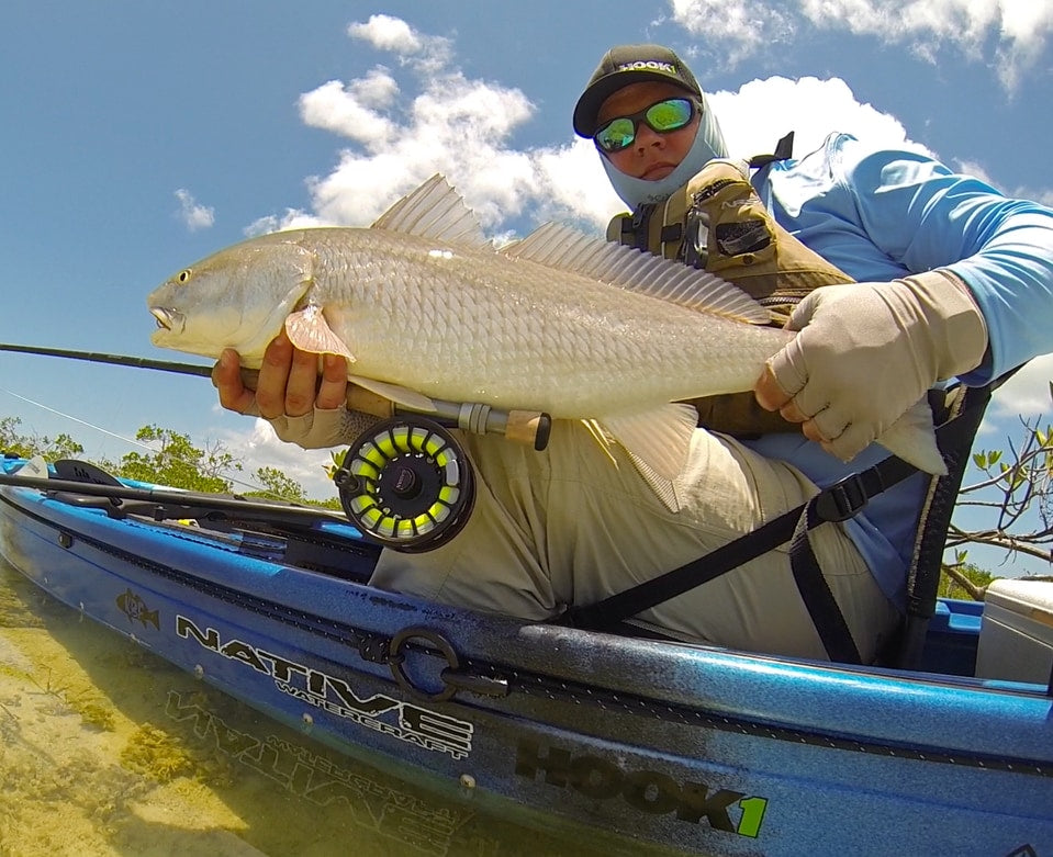 Angler holding fish caught in a Native Watercraft Ultimate FX 15