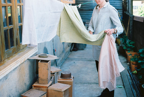 Our founder, Josie, hanging up naturally dyed fabric on a washing line outside our workshop