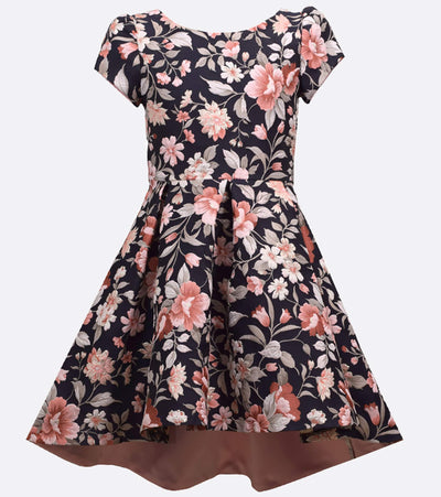Short sleeve floral jacquard dress with metallic accents, pleated hi-low skirt, self back ties, and contrast satin lining.